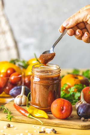 Homemade DIY natural canned hot plum sauce chutney with chilli or tkemali in glass jar standing on wooden table with ingredients.