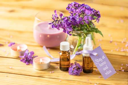 Stay at home and relax text phrase on label sticker. Spa still life with violet oil, towel and perfumed candle on natural wood table surface. Quarantine coronavirus life concept