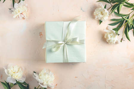 Gift on light concrete table surface surrounded beautiful white peony flowers. Top view, flat lay, greeting card.