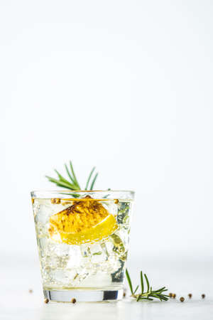 Glass of Charred Lemon, Rosemary and Coriander Gin and Tonic is a flavors are perfectly balanced refreshing cocktail. on light background, close up. Summer drinks and alcoholic cocktails