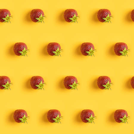 Diagonal pattern from ripe juicy strawberries on bright yellow background. Creative minimalist flat lay. Vitamins vegan healthy diet concept