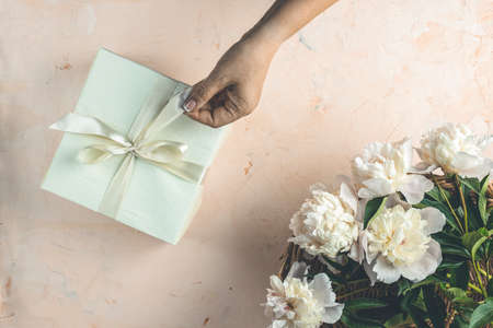 Womans hands hold ribbon for gift on light concrete table surface surrounded beautiful white peony flowers. Top view, flat lay, greeting card.