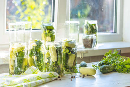 Fresh cucumbers ready to be pickled. Marinated preserving jars. Homemade white and green cucumber  pickles with basil, fresh parsley, dill, spices near window in the sunny summertime. 写真素材