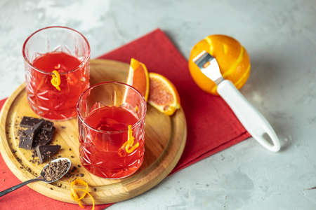 Two glasses of chocolate red orange negroni, alcoholic bitter cocktail served by ingredients on the light gray table.