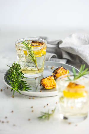 Glasses of Gin and Tonic with Charred Lemon, Rosemary and Coriander is a flavors are perfectly balanced refreshing cocktail. on light background, close up surrounded ingredients, selective focus