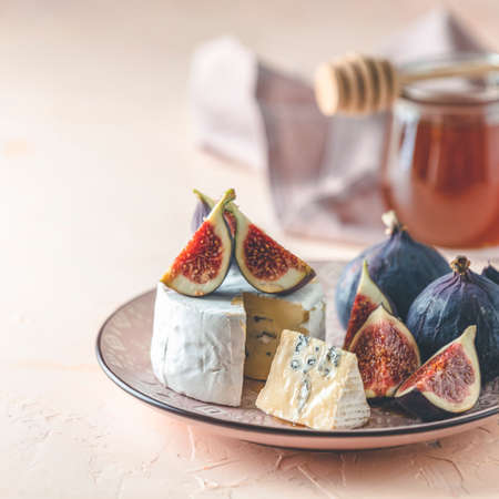 Blue or bleu cheese with fig and honey or maple syrup on pink plate. Tasty white cheese close up view.