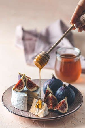 Sweet honey dripping from blue or bleu cheese with fig and honey or maple syrup on pink plate. Tasty white cheese close up view.
