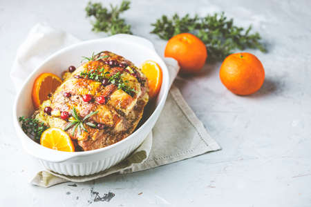 Roasted pork in white dish, christmas baked ham with cranberries, tangerines, thyme, rosemary, garlic on light table surface.