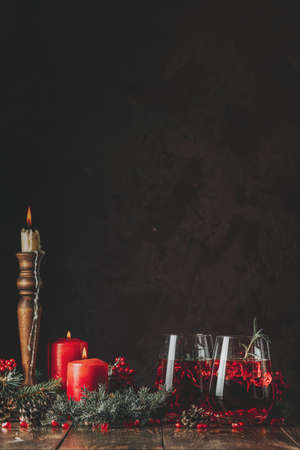 Greeting food Christmas and New Year composition. Two glasses of pomegranate drink surrounded pine branches and festive candles, dark background. 写真素材