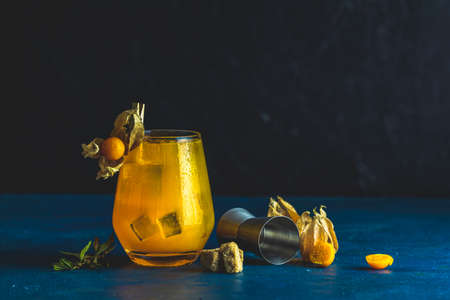 Yellow orange cocktail with tangerine and rosemary in glass with water drops decorated Physalis peruviana and brown sugar on dark background. Christmas and New Year holiday welcome drink