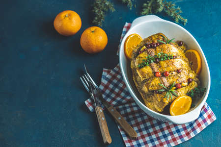 Roasted pork in white dish, christmas baked ham with cranberries, tangerines, thyme, rosemary, garlic on dark blue table surface