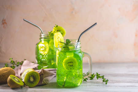Glass jar of kiwi juice or smoothie. Kiwi Mojito cocktail or non-alcohol mocktail with mint and sliced kiwi fruits on wooden background copy space 写真素材