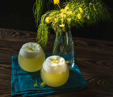 Two glasses of fennel flower cocktail with organic egg white, fennel pollen and fennel flower garnish. Scene is illuminated by beautiful evening sunlight.