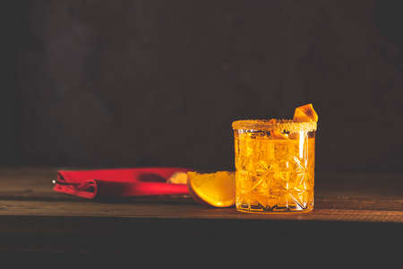 Cocktail Negroni on a old wooden board. Drink with gin, orange, an italian cocktail, an aperitif, first mixed in Firenze, Italy, in 1919, alcoholic bitter cocktail
