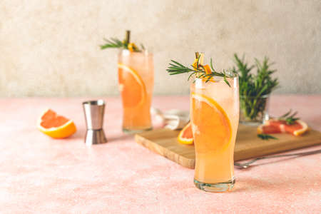 Two highball glasses of Paloma cocktails with tequila fresh grapefruit juice combined and rosemary. Surrounded of ingredients and bar tools. Light pink concrete surface.