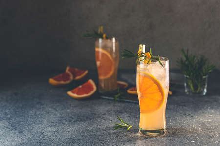 Two highball glasses of Paloma cocktails with tequila fresh grapefruit juice combined and rosemary. Dark gray concrete surface.