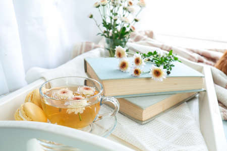 Cup of tea, books, chrysanthemum flowers and macaroons in tray on the table. Cozy home concept. Coloring and processing photo Stock Photo