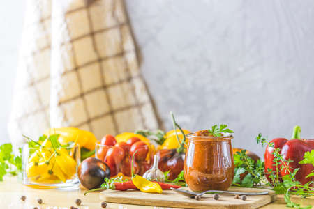 Homemade DIY natural canned hot plum sauce chutney with chilli or tkemali in glass jar standing on wooden table with ingredients. Selective focus. Stock Photo