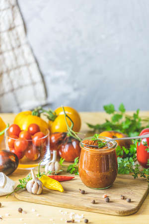 Homemade DIY natural canned hot plum sauce chutney with chilli or tkemali in glass jar standing on wooden table with ingredients. Selective focus. Stock Photo - 166327768