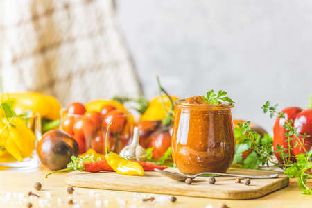 Homemade DIY natural canned hot plum sauce chutney with chilli or tkemali in glass jar standing on wooden table with ingredients. Selective focus. Stock Photo - 166327788