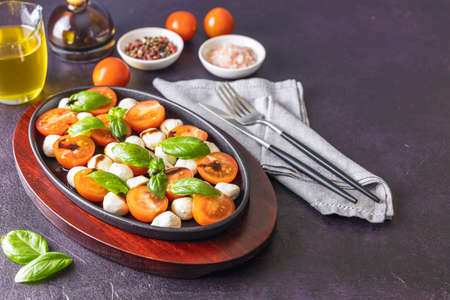 Caprese salad with cherry tomatoes, mozzarella and basil in oval black plate. Close up, copy space for your text Stock Photo