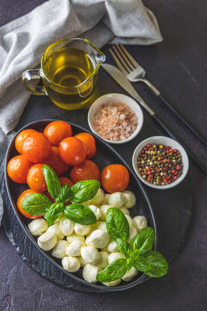 Mozzarella cheese, basil and tomato cherry in oval black plate, copy space. Ingredients for Caprese salad