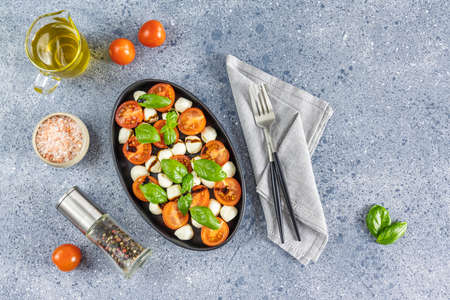 Caprese salad with cherry tomatoes, mozzarella and basil in oval black plate. Top view with space for your text