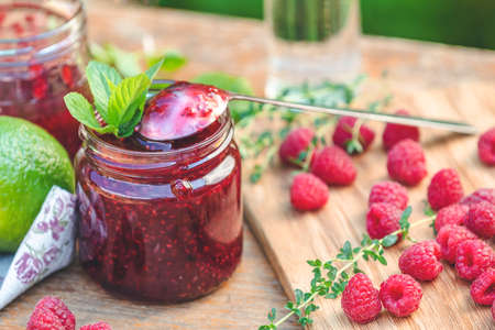 Raspberry jam and fresh raspberry on a rustic wooden table in the garden. Summer sunny day, close up, shallow depth of the field. Stock Photo - 166535076