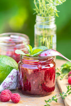 Raspberry jam and fresh raspberry on a rustic wooden table in the garden. Summer sunny day, close up, shallow depth of the field. Stock Photo