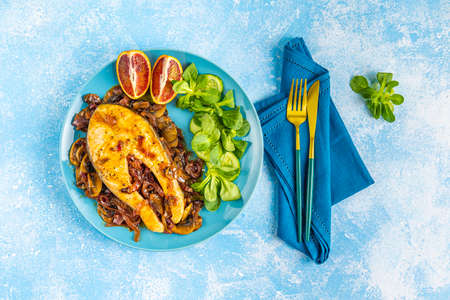 Baked salmon steak with mushroom, onion and spices served with ingredients on light blue table surface. Top view, copy space for you text.