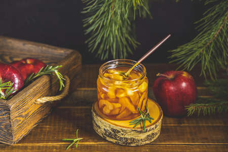 Apple jam or marmalade in jar on dark wooden table surface. Organic healthy vegetarian food, concept of holiday.