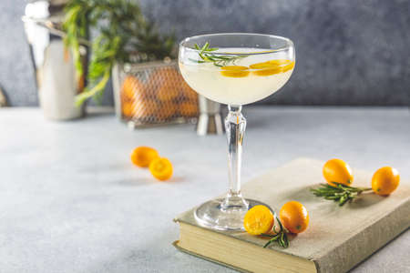 Gin and tonic cocktail with kumquat fortunella in glass of champagne on light gray table surface. Close up, shallow depth of the field.