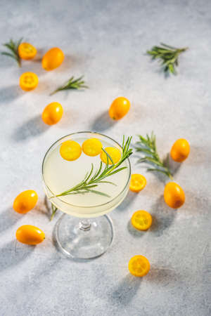 Gin and tonic cocktail with kumquat fortunella in glass of champagne on light gray table surface. Close up, shallow depth of the field. Stock Photo - 167055248