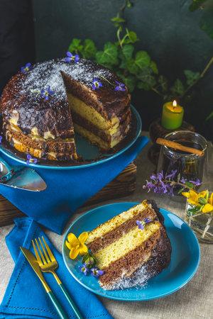 Plate with slice of tasty homemade chocolate sponge cake on table. Chocolate cake food photography recipe idea