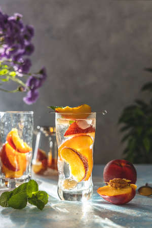 Summer cold peach fizz cocktail or iced tea with mint. Sunny light, light concrete table surface. Shallow depth of the field, close up, copy space for you text. Standard-Bild