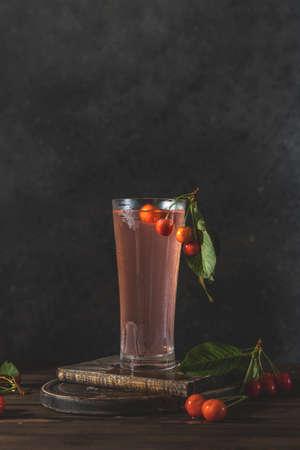 Glass of many cherry or merry berries lemonade water with splash, surround of fresh cherry or merry berries. Dark rustic wooden surface