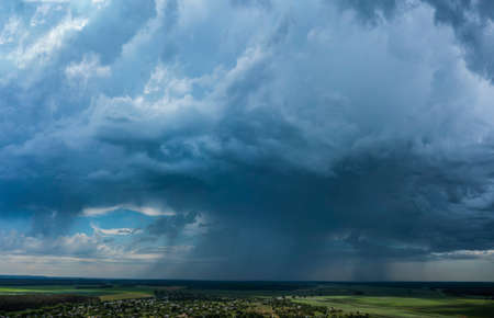 Aerial Flying over countryside with village, forest, ponds, and fields at summer time under dramatic rain cloud. Global warming effect black thunderstorm dramatic rain clouds, dramatic sky. Standard-Bild