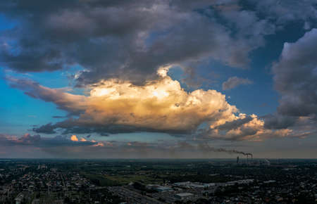 Panoramic view dramatic sky over city. Far village sight under cloudy sky. Aerial Flying over town, far industrial sight beyond. Standard-Bild