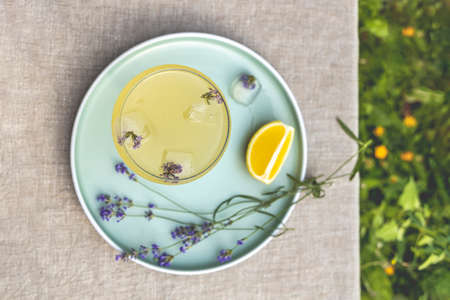 Top view Pompadour glass of lavender lemonade with cube ice with lavender flowers. Table in summer garden. Standard-Bild