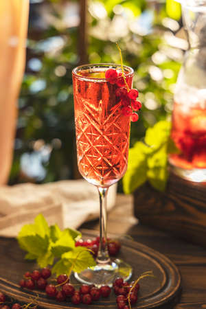Glass of fresh cold currant cocktail on the table near the window, sunny backlight. Dark wooden style, close up, shallow depth of the field.