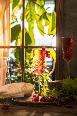 Glass of fresh cold currant cocktail on the table near the window, sunny backlight. Dark wooden style, shallow depth of the field.