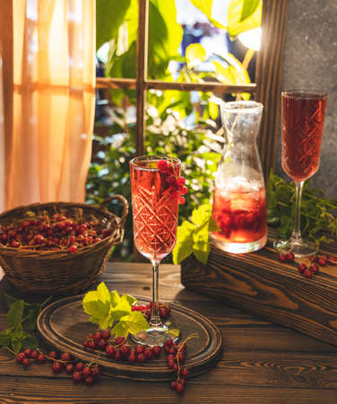 Two glass and jug of fresh cold currant cocktail on the table near the window, sunny backlight. Dark wooden style.