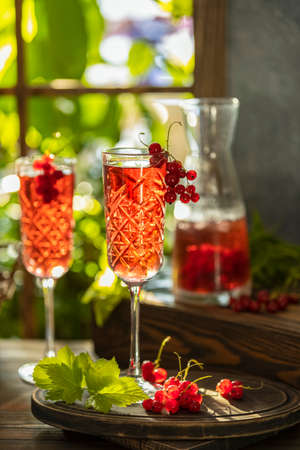 Two glasses of fresh cold currant cocktail on the table near the window, sunny backlight. Dark wooden style, shallow depth of the field.