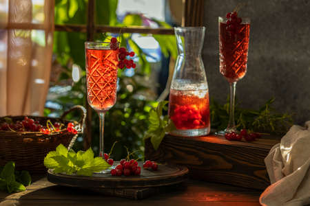 Two glasses and jug of fresh cold currant cocktail on the table near the window with sunny backlight. Dark wooden rustic style.