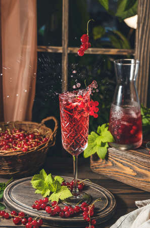Glass and jug of fresh cold currant cocktail with splash and fly berries on the table near the window. Dark wooden rustic style. Standard-Bild