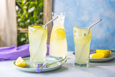 Glasses of lavender lemonade with cube ice with lavender flowers on the table near window  in the sun summertime. Standard-Bild