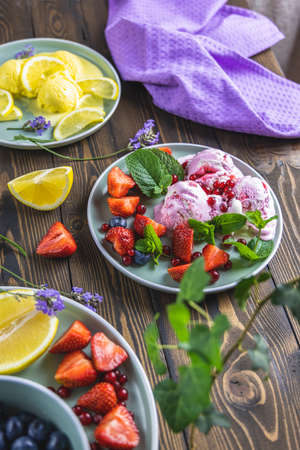 Different ice cream sorbet. Lemon and lavender, strawberry, red currant and blueberry ice cream in plates on dark wooden table surface. Dark rustic style.