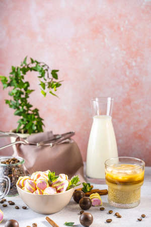 Pot of marshmallow and glass of brew cold coffee and ice. Cold summer drink on a light gray table surrounded coffee beans, bottle of milk chocolate candy, cinnamon and fresh mint. Standard-Bild