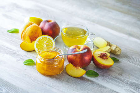 Fresh homemade peach jam in glass jar on a wooden background. Several fresh berries, lemon and mint are near it, close up, shallow depth of the field.