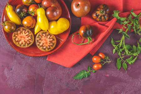 Colorful tomatoes in red ceramic plates on dark red concrete surface. Concept of green house life style and products of subsistence farming, flat lay, copy space for you text